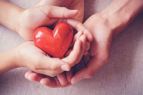 Des mains qui portent un coeur rouge