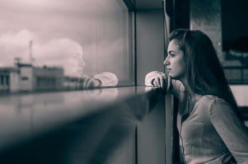Une femme regarde par la fenêtre et pense à sa relation à distance