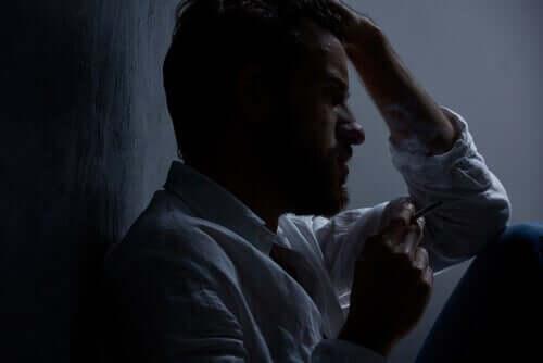 Un homme assis dans le noir pris par l'anxiété