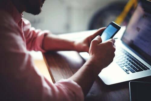 Un homme avec un ordinateur et un téléphone