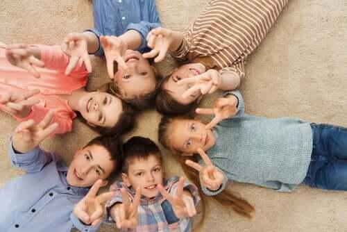 Des enfants allongés sur le dos faisant le signe de la paix