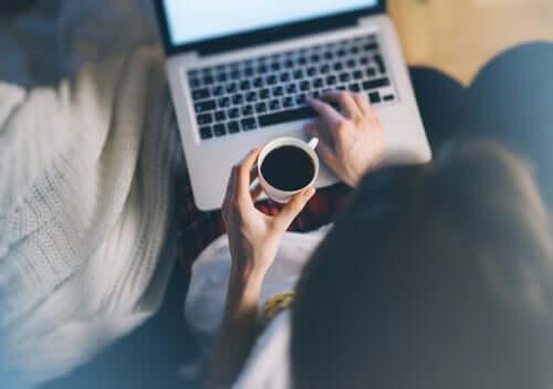 Une femme avec son café sur son ordinateur