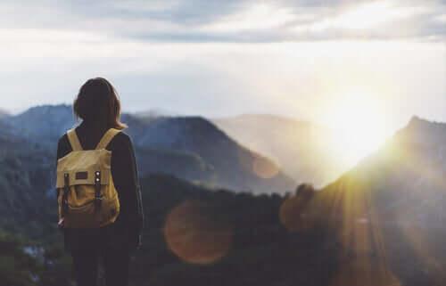 Une femme en voyage regarde la montagne au loin