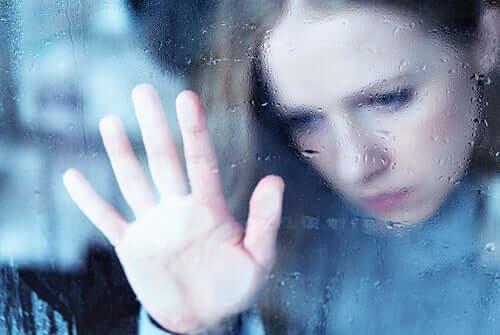 Une femme posant une main à la fenêtre triste à cause de l'anxiété