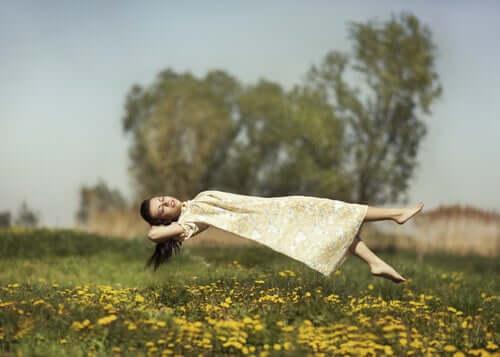 Une fille qui lévite dans un champ