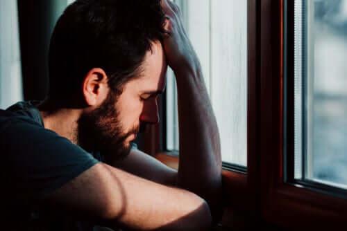 Un homme appuyé à la fenêtre envahi par l'anxiété
