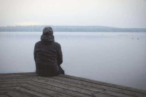 Un homme assis devant un lac