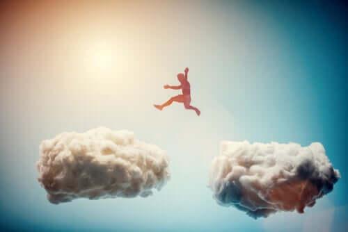 Un homme qui saute par-dessus les nuages et qui sort de la zone de confort