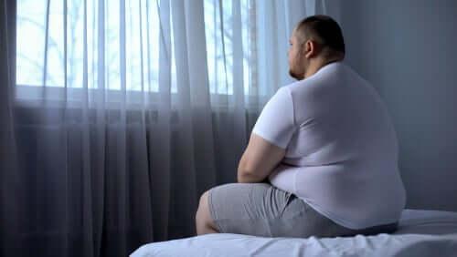 Un homme assis sur le lit regardant par la fenêtre