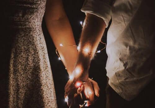 Deux personnes se tenant la main avec une guirlande lumineuse enroulée autour de leur bras