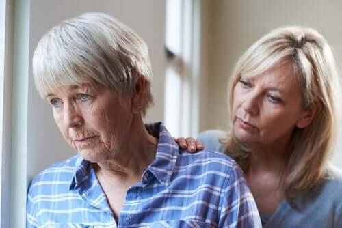 Une femme posant la main sur l'épaule de sa mère souffrant de démence corticale
