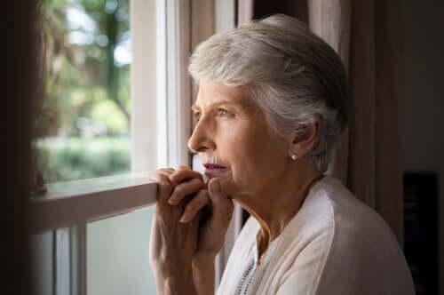 Une femme touchée par la démence corticale regardant par la fenêtre