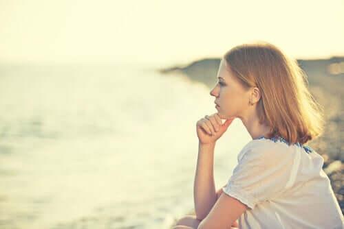Une femme réfléchissant face à la mer
