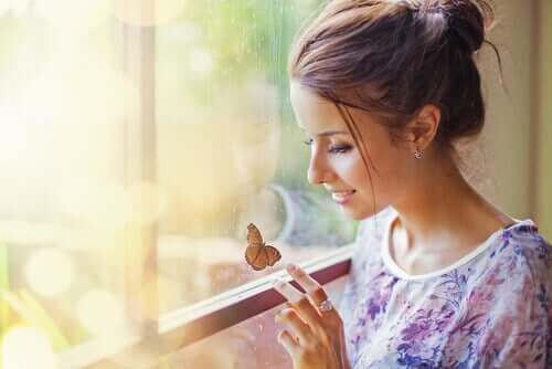 Une femme qui sourit en voyant un papillon.