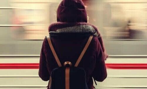 Un train passe devant une femme