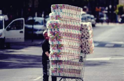 Un homme avec un chariot rempli de papier toilette