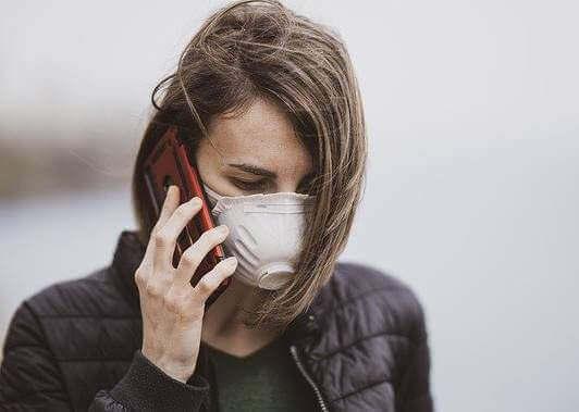 Une femme avec un masque au téléphone