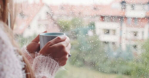 Une femme à sa fenêtre avec un café tentant d'affronter l'isolement
