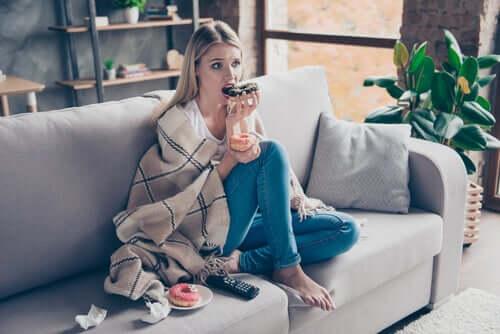 Une femme en train de manger des donuts du fait du lien stress et alimentation