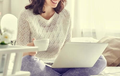 Une femme sur son ordinateur en pyjama
