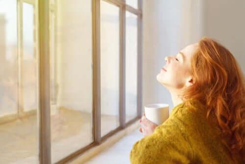 Une femme devant sa fenêtre buvant un café pendant le confinement