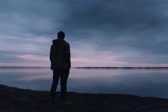 Un homme est debout face à la mer se posant des questions du fait de la dépression existentielle