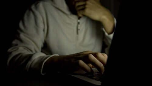Un homme regardant de la pornographie sur son ordinateur dans le noir