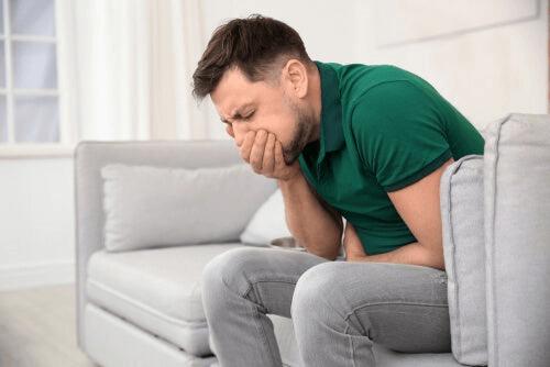 Un homme sur le point de vomir car le dégoût l'habite