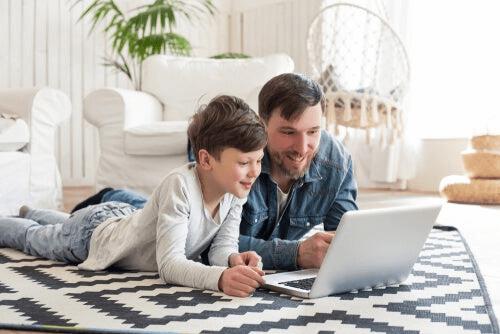 Un enfant et son père devant un ordinateur pendant la pandémie