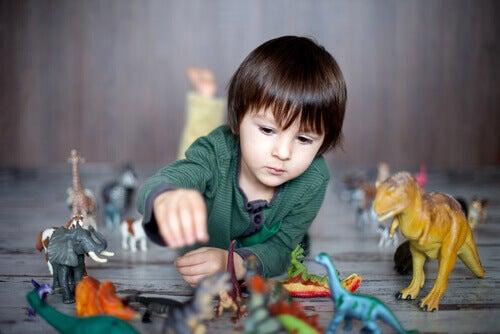 Un enfant ayant de hautes capacités intellectuelles jouant avec des dinosaures