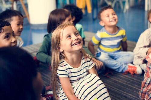 Des enfants souriants en classe face à l'arbre des valeurs