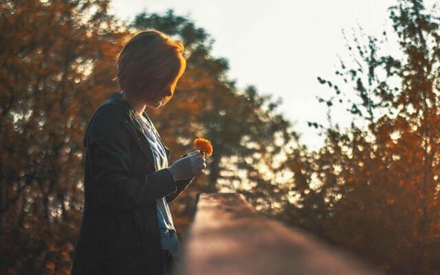 Une femme regarde par terre en tenant une fleur.
