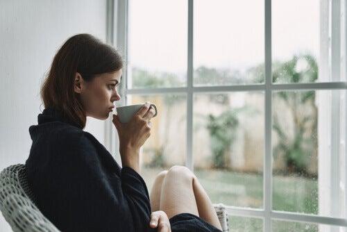 Une femme buvant dans une tasse face à une fenêtre pendant le confinement