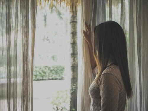 Une femme regardant par la fenêtre durant le confinement