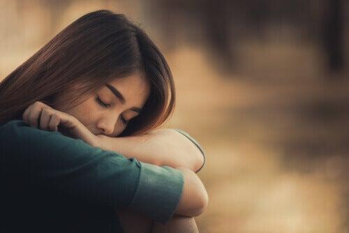 Une femme pose sa tête contre ses genoux