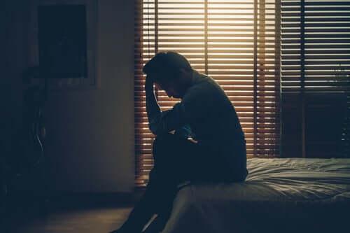 Un homme pleurant sur son lit car en deuil
