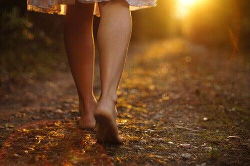 Une femme marchant pieds nus représentant le fait d'aller de l'avant