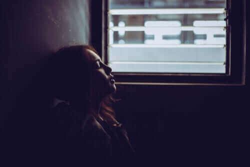 Une femme adossée au mur.