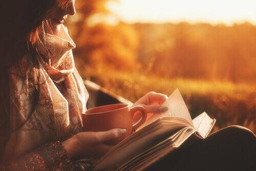 Une femme lisant un livre au coucher du soleil