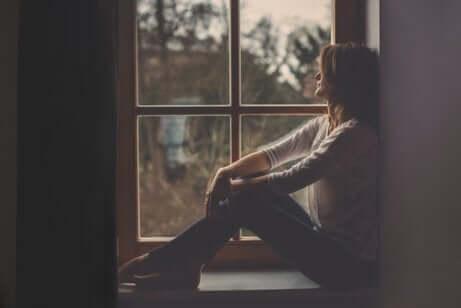 Une femme au bord d'une fenêtre pensant aux phrases de Miguel Delibes