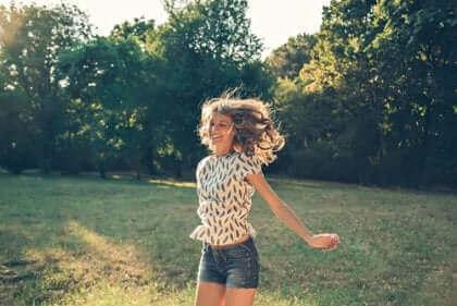 Une femme courant dans un champ heureuse.
