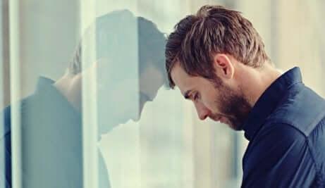 Un homme posant la tête sur une vitre et la rigidité.