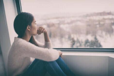 Une femme morose regardant le jour gris par la fenêtre.