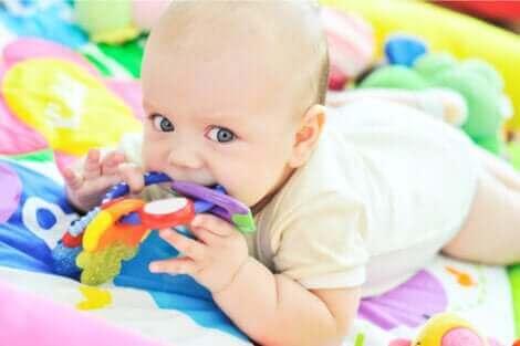 Un bébé qui joue allongé par terre.