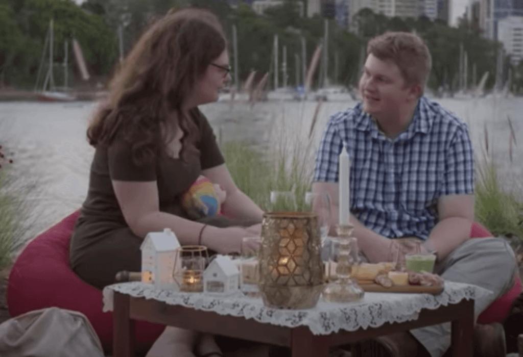 Un couple qui déjeune au bord d'une rivière.