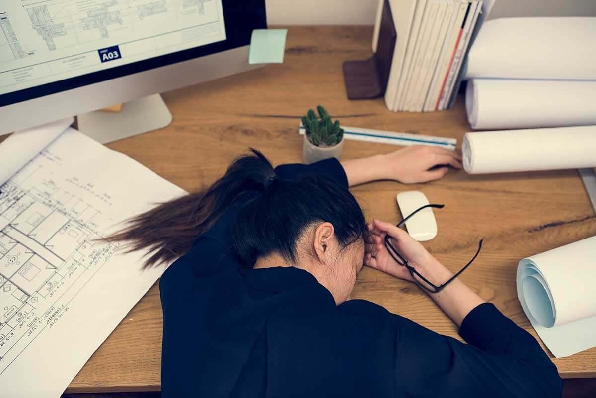 Une femme épuisée affalée sur son bureau.