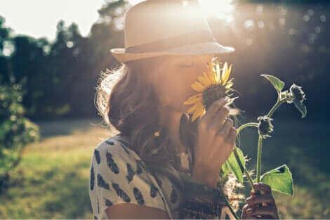 Une femme en train de sentir une fleur.