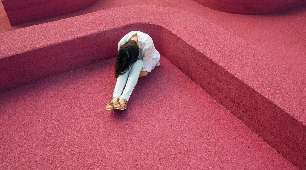 Une femme triste assise par terre.