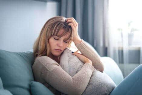 Une femme triste affalée sur le canapé.