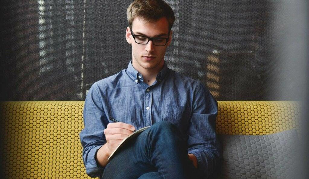 Un homme assis sur le canapé en train de procrastiner.